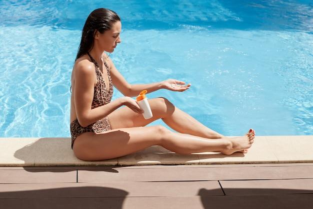 Férias de verão, moda, conceito de férias. tiro ao ar livre de uma jovem mulher bonita com atrasos longslim no cais de madeira na piscina, aplicar protetor solar no corpo perfeito, feminino vestindo maiô com estampa de leopardo