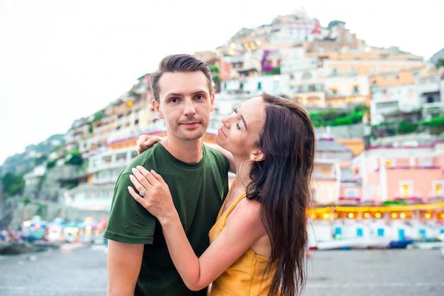 Férias de verão na itália. casal jovem na vila de positano no fundo, costa amalfitana, itália