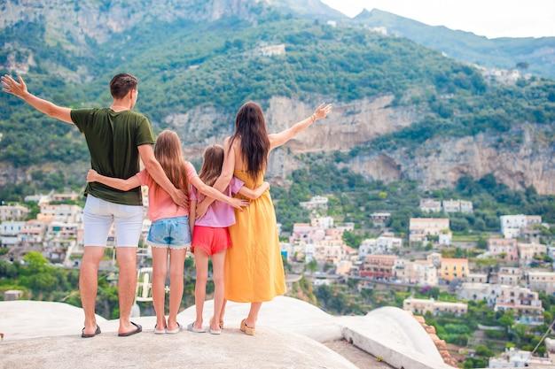 Férias de verão na itália. jovem mulher na vila de positano no fundo, costa amalfitana, itália