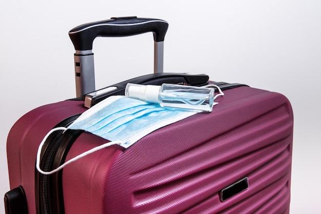 Férias de verão no novo normal, preparado para viajar, mala com máscara médica protetora, gel desinfetante para as mãos na bagagem, proteger.
