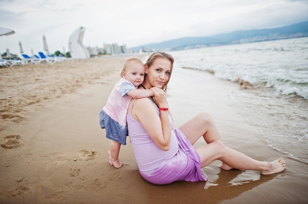 Férias de verão. pais e pessoas atividade ao ar livre com crianças. boas férias em família. mãe grávida com filha bebê na praia de areia do mar.
