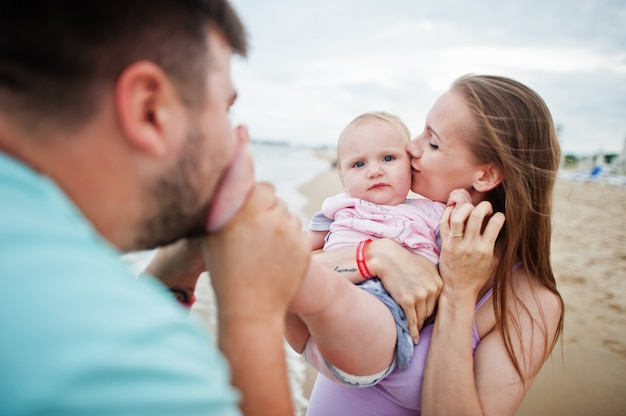Férias de verão. pais e pessoas atividade ao ar livre com crianças. boas férias em família. pai, mãe grávida, filha bebê na praia de areia do mar.