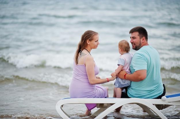 Férias de verão. pais e pessoas atividade ao ar livre com crianças. boas férias em família. pai, mãe grávida, filha sentada na espreguiçadeira na praia de areia do mar.