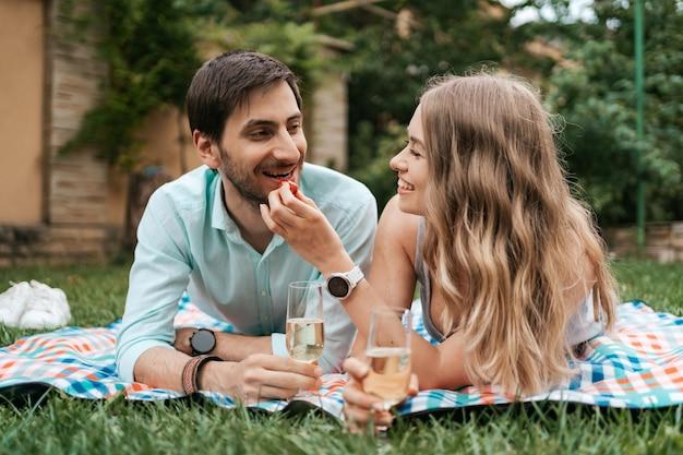 Férias de verão, pessoas, romance, homem e mulher se alimentando de morangos enquanto bebem espumantes e aproveitam o tempo juntos em casa