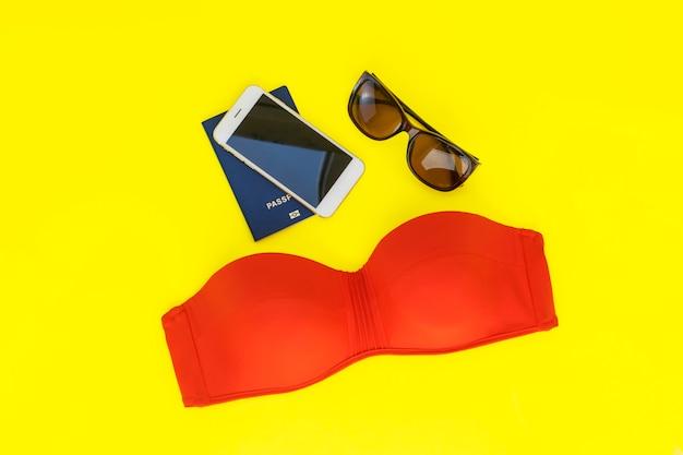 Férias de verão viagem plana leigos. olá verão. desejo de viajar. maiô vermelho, óculos, passaporte em um fundo amarelo