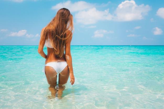 Férias de verão - vista traseira de uma loira sexy caucasiana de biquíni na lagoa azul da praia de areia branca