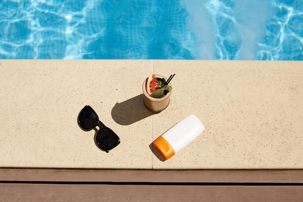 Férias de verão, vocação, relaxamento, felicidade, conceito de moda. as coisas da mulher no cais de madeira na piscina no spa, óculos de sol pretos, protetor solar e coquetel perto da água na piscina do resort de luxo.