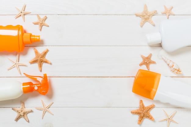 Férias de viagem de verão conceito plana leigos. frascos de protetor solar com estrela do mar na mesa de madeira branca com espaço de cópia.