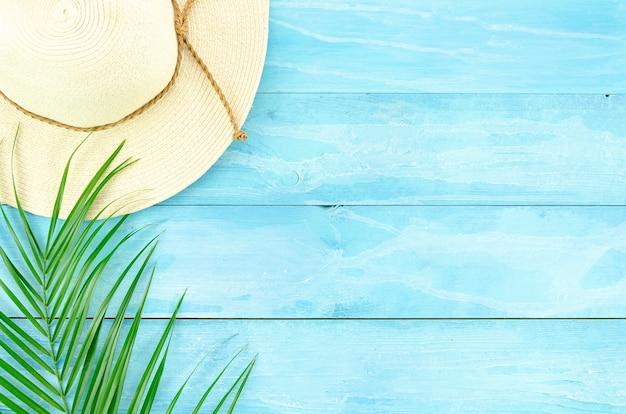 Férias de viagem vista superior fundo azul e folha de palmeira tropical