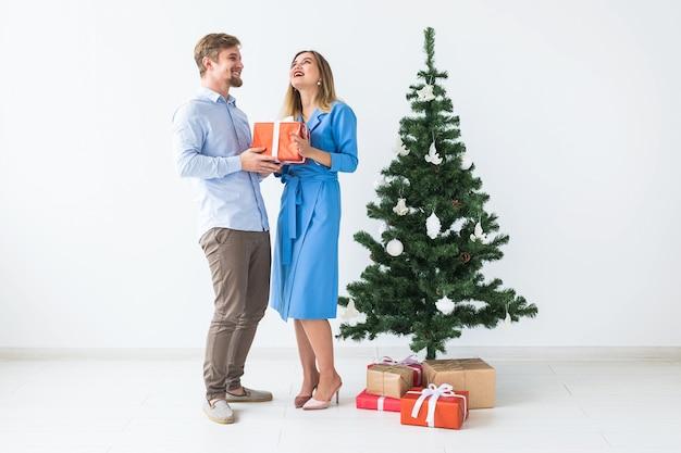 Férias e conceito de celebração - homem dando um presente de natal para a namorada.