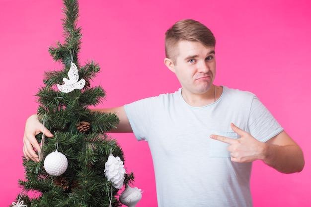 Férias e conceito de pessoas - homem feliz com árvore de natal na parede rosa.