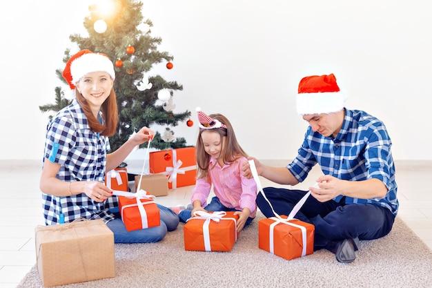 Férias e presentes conceito - retrato de uma família feliz abrindo presentes na época do natal.