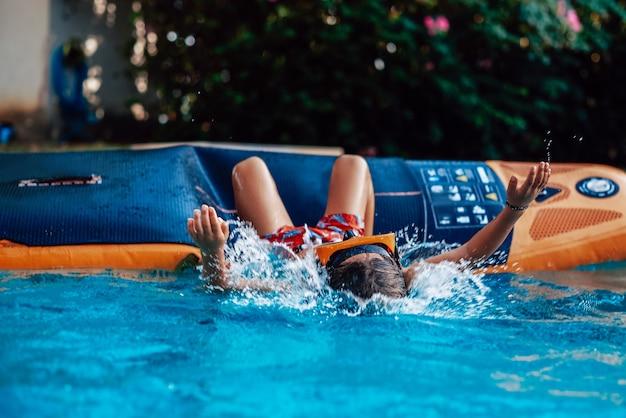 Férias e recreação na tailândia. criança brincalhona com óculos de proteção cai na água com as mãos estendidas.