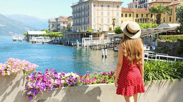 Férias em bellagio. vista traseira da jovem apreciar a vista da cidade de bellagio no lago de como, itália.