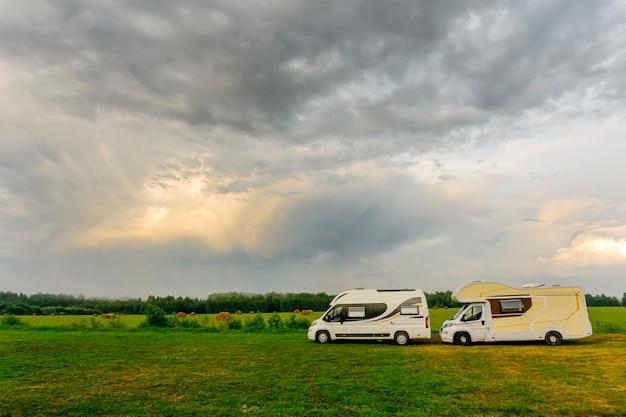 Férias em família e viagens (viagem) ao ar livre de motorhome (caravan car). dois motorhomes em um acampamento de verão ao ar livre. viajar (viagem) pelo conceito de carro.