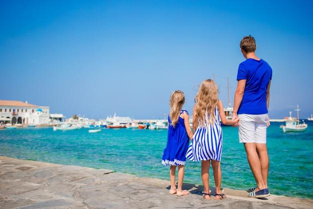Férias em família na europa. pai e filhos na cidade de mykonos na grécia