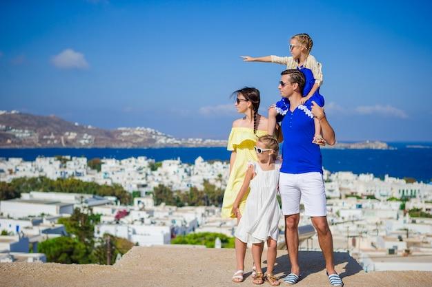 Férias em família na europa. pais e filhos a olhar para a paisagem urbana da ilha de mykonos, na grécia
