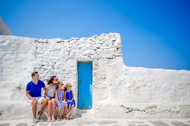Férias em família na europa. pais e filhos na rua da aldeia tradicional grega típica com paredes brancas e portas coloridas na ilha de mykonos, na grécia