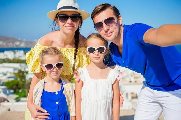 Férias em família na europa. pais e filhos tomando selfie na cidade de mykonos, na grécia