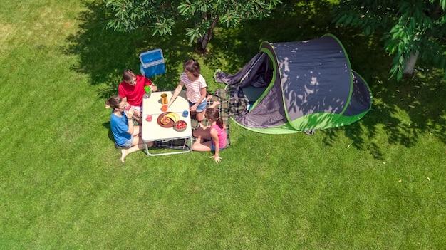 Férias em família no acampamento com vista aérea de cima, pais e filhos relaxam e se divertem no parque, barraca e equipamento de acampamento sob a árvore, conceito família no acampamento ao ar livre