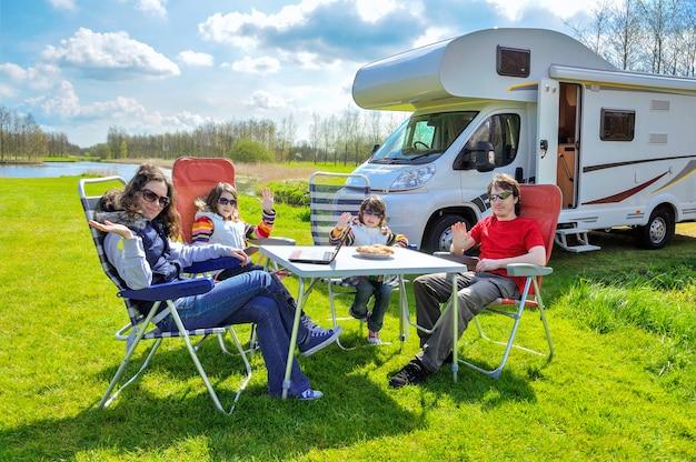 Férias em família, rv (campista) viajam com crianças, pais felizes com crianças sentam-se à mesa no acampamento