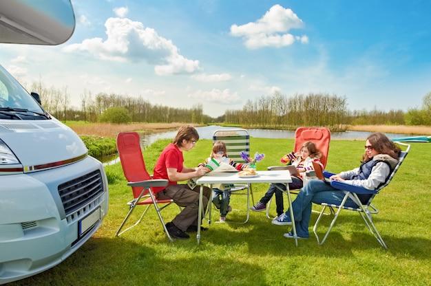 Férias em família, viagens de rv com crianças, pais felizes com crianças se divertem na viagem de férias no motorhome