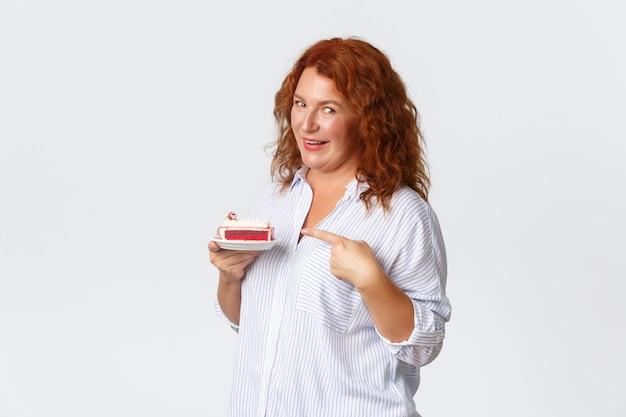 Férias, emoções e conceito de estilo de vida. sorrindo satisfeita, uma linda mulher de meia-idade recomenda a melhor sobremesa da cidade, apontando o dedo para o bolo, visite o café favorito, em pé na parede branca.