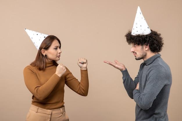 Férias festivas e conceito de festa - feliz emocional animado surpreso adorável jovem casal brigando um com o outro na filmagem cinza