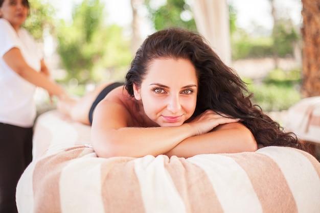 Férias, mulher bonita no salão spa na praia ensolarada receber massagem de rosto e costas