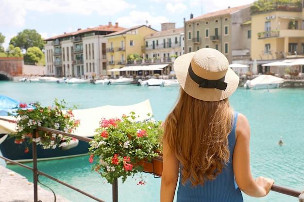Férias na europa. vista traseira da menina bonita da moda apreciando a visita ao lago de garda. férias de verão na itália.