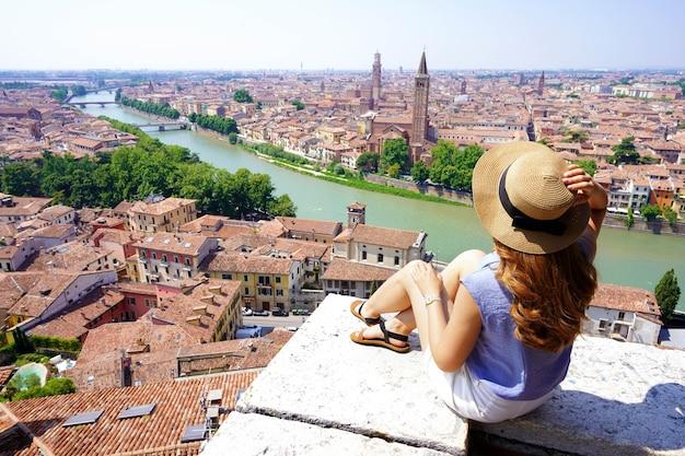 Férias na itália. mulher atraente sentada na parede, olhando a deslumbrante vista da cidade de verona, itália.