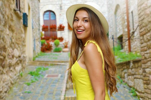 Férias na itália. retrato de jovem com chapéu e vestido amarelo, andando na vila italiana de assis, umbria.