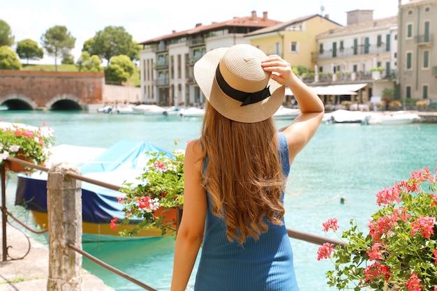 Férias na itália. vista traseira da menina bonita da moda caminhando em peschiera del garda. férias de verão na europa.