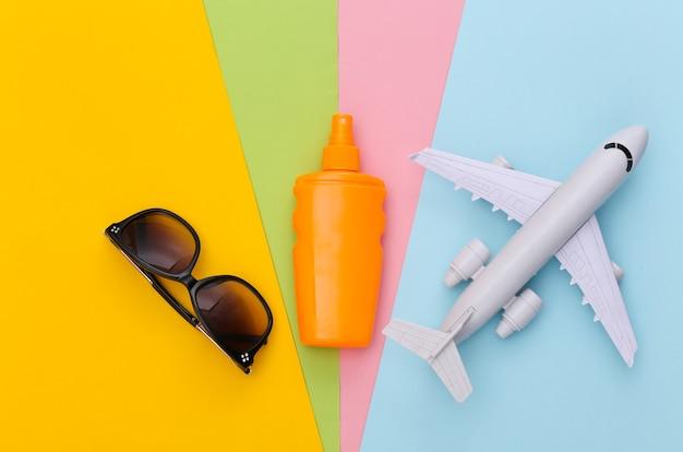 Férias na praia, conceito de viagens. frasco de protetor solar, aeroplano e câmera