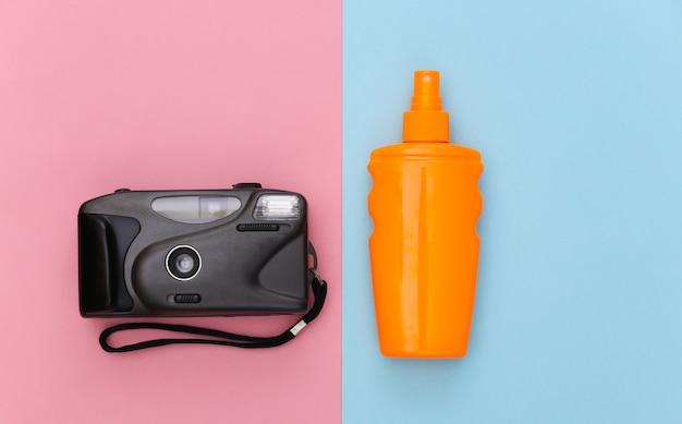Férias na praia, conceito de viagens. frasco de protetor solar e câmera em rosa azul