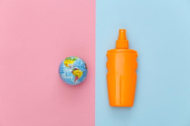 Férias na praia, conceito de viagens. frasco de protetor solar e globo em rosa azul