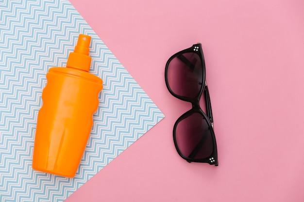 Férias na praia, conceito de viagens. frasco de protetor solar e óculos de sol em rosa azul