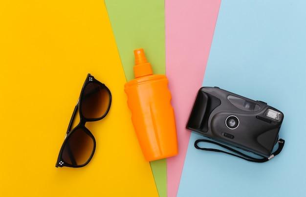 Férias na praia, conceito de viagens. frasco protetor solar, óculos de sol e câmera