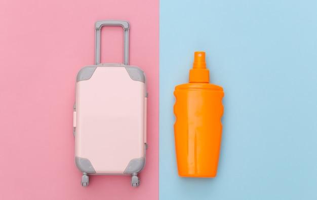 Férias na praia, conceito de viagens. mini-brinquedo de bagagem de viagem e frasco de protetor solar em azul rosa