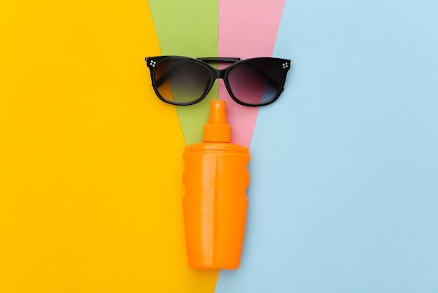 Férias na praia. frasco protetor solar e óculos de sol