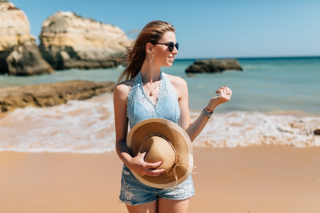 Férias na praia. linda mulher de chapéu de sol, aproveitando o dia de sol perfeito, caminhando na praia. felicidade e bem-aventurança.