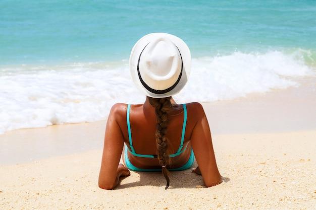 Férias na praia. slim linda mulher em sunhat e biquíni azul deitado