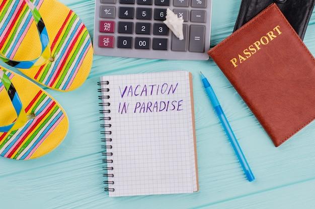 Férias no paraíso escritas em caderno, chinelos e passaporte. férias de planejamento de conceito.