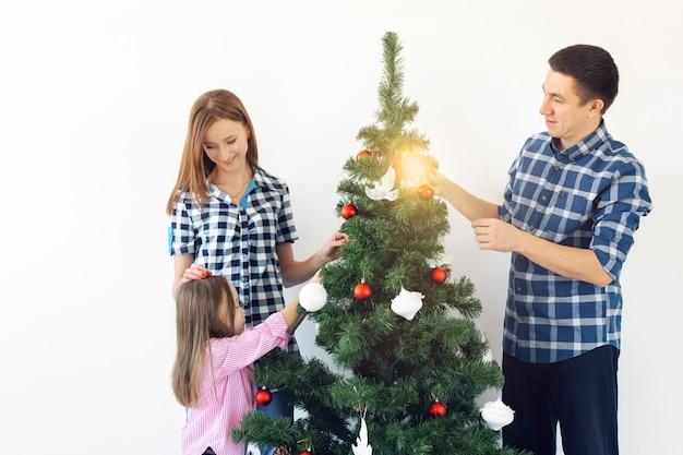Férias, pais e comemorando o conceito - família feliz, decorando uma árvore de natal com bugigangas na sala de estar em fundo branco.