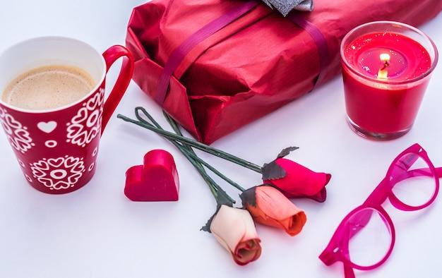 Férias para pessoas apaixonadas dia dos namorados copo vermelho com velas e presentes de flores rosas de café