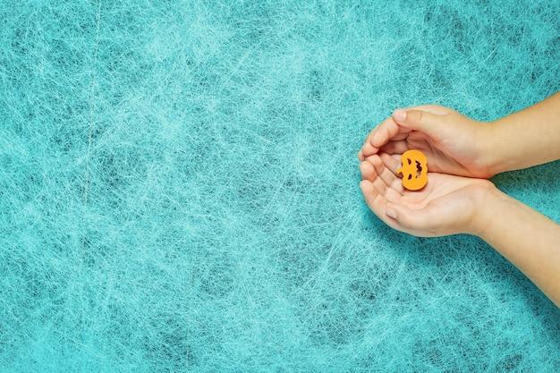 Férias rindo sobre um fundo de teia de aranha com uma abóbora nas mãos de uma criança