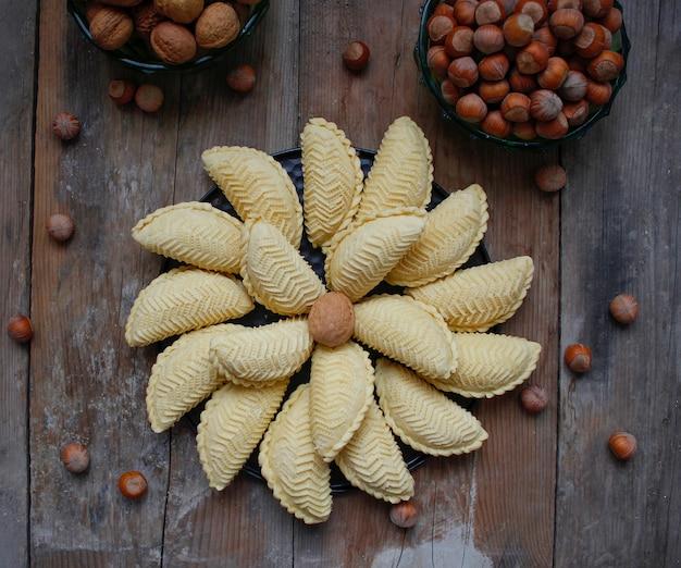 Férias tradicionais do azerbaijão cookies de nowruz na placa preta sobre o rústico com nozes