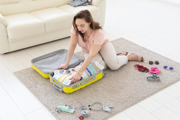 Férias, viagem e conceito de viagens - jovem arrecada uma mala em casa no quarto, muito
