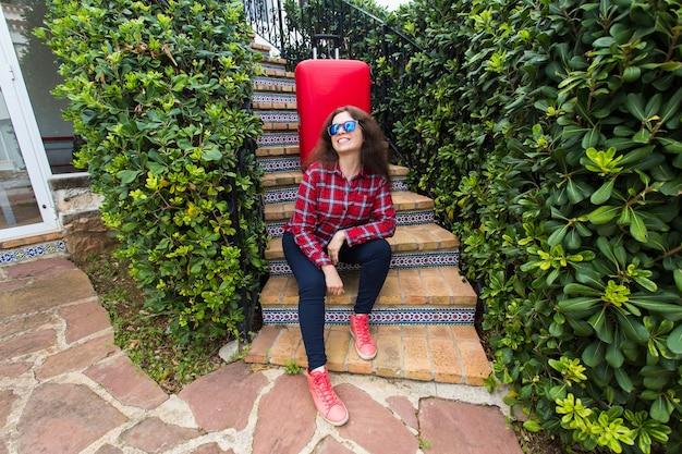 Férias, viagens, conceito de pessoas. jovem de óculos escuros, sentado na escada com malas e sorrindo.