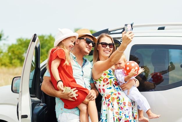 Férias, viagens - família feliz e pronta para a viagem para as férias de verão. as pessoas se divertem e tiram fotos no telefone. tire uma selfie na memória da viagem